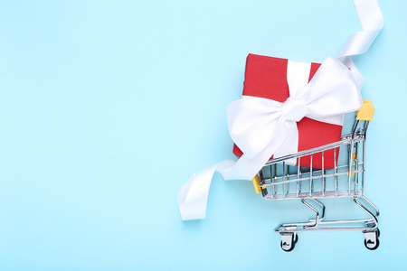 Small shopping cart with gift box on blue background