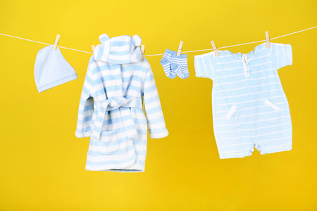 Baby clothes hanging on yellow background