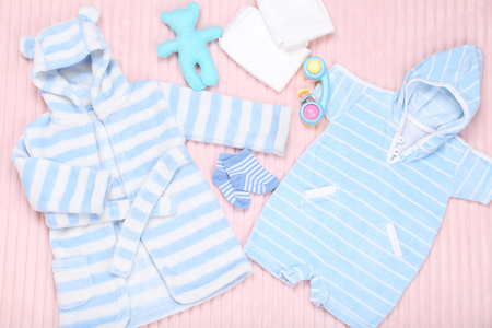 Baby clothes with toys and diapers on pink background