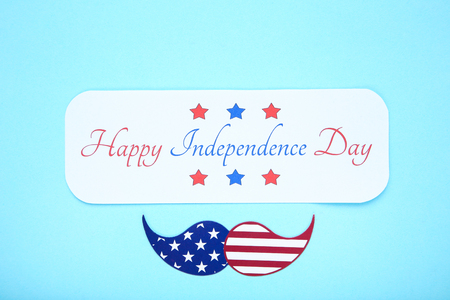 Text Happy Independence Day with paper mustache on blue background Imagens