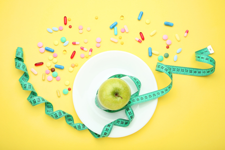 Green measuring tape with pills and sweet apple on yellow background Stok Fotoğraf