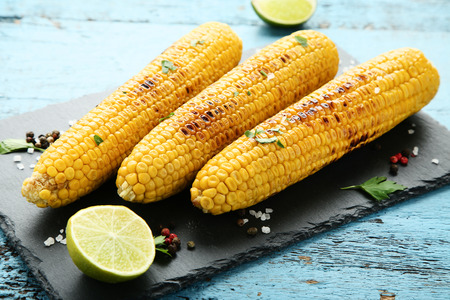 Grilled corn with lime pieces and seasonings on wooden table
