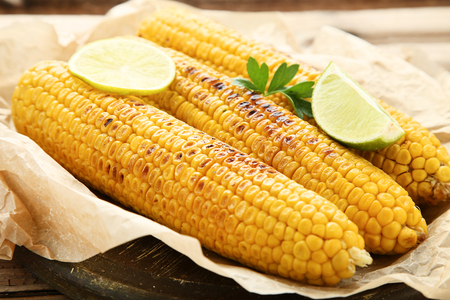 Grilled corn with parsley leaf and lime on wooden table Archivio Fotografico