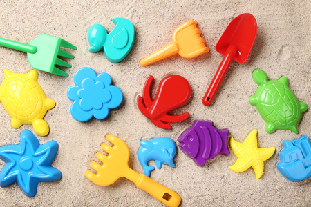 Colorful plastic toys on beach sand Stockfoto