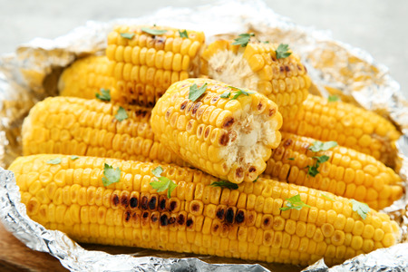 Grilled corn with green parsley in foil
