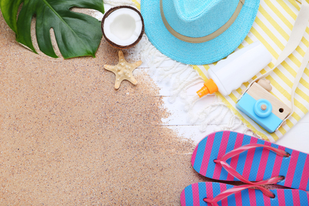 Fashion clothing with sunscreen and coconut fruit on white wooden table