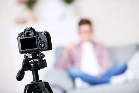 Jonge jongen zit op de bank en neemt video op