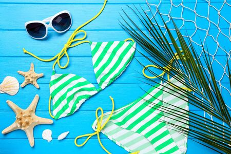 Fashion swimsuit with palm leaf and seashells on blue wooden table