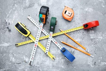 Ruletas de construcción con lápices sobre mesa de madera gris