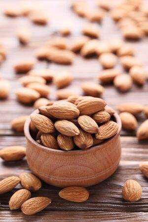Almonds in bowl on brown wooden table