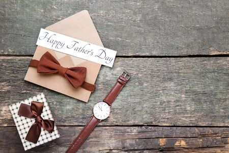 Text Happy Fathers Day with gift box and wrist watch on wooden table