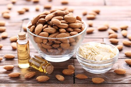 Almond and oil in bottles on brown wooden table Stockfoto