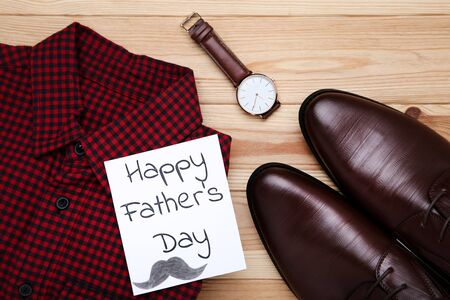 Text Happy Fathers Day with red shirt, male shoes and wrist watch on wooden table