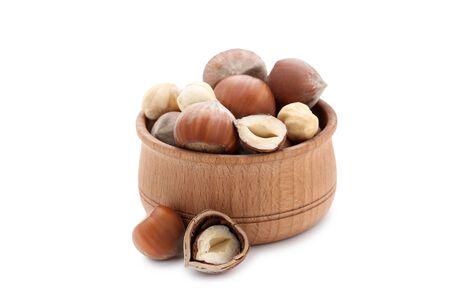 Hazelnuts in bowl isolated on white background