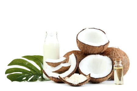 Coconut milk in bottle with oil and monstera leaf on white background
