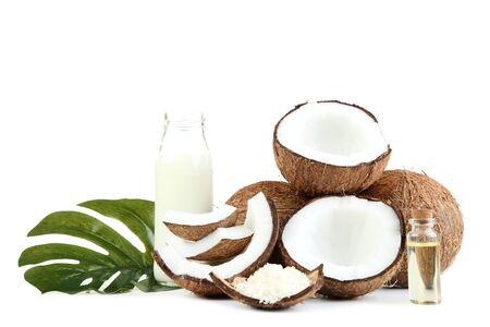 Kokosmilch in der Flasche mit Öl und Monstera-Blatt auf weißem Hintergrund