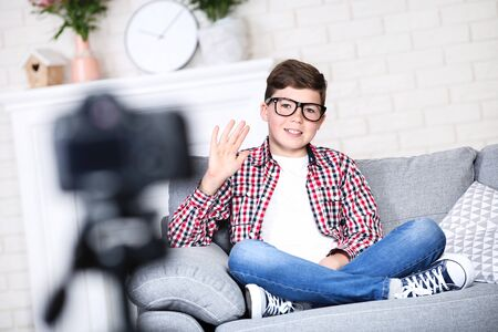 Young boy sitting on sofa and records video