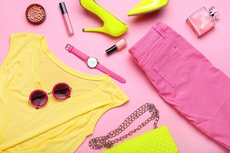 Modern women's clothes with accessories on pink background