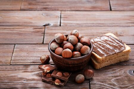Bread with melted chocolate and hazelnuts on wooden table 写真素材
