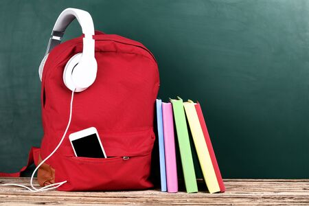 School backpack with headphones, smartphone and books on brown wooden table