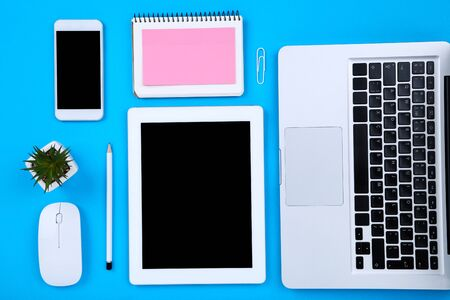 Tablet, laptop computer with smartphone, mouse, notepad and green plant on blue background