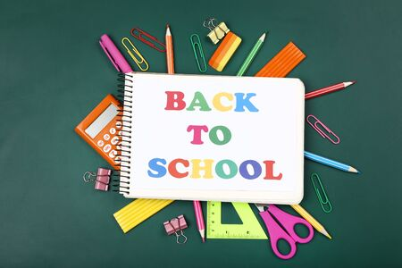 Text Back To School with stationery on green background