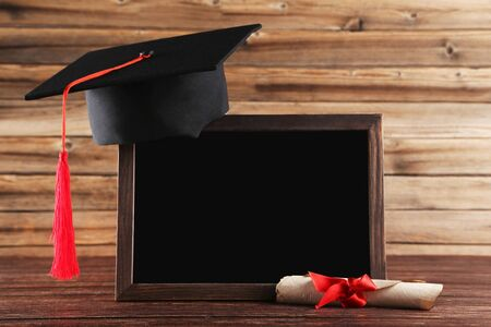 Graduation cap with diploma and blank frame on brown wooden table
