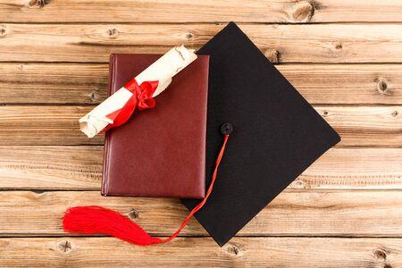 Abschlusskappe mit Diplom und Buch auf braunem Holztisch