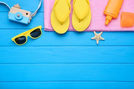 Modekleidung mit Seestern und Sonnencreme auf blauem Holztisch Standard-Bild