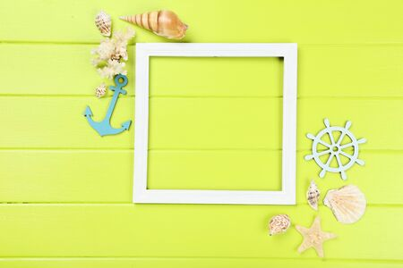 Wooden blank frame with seashells on green table