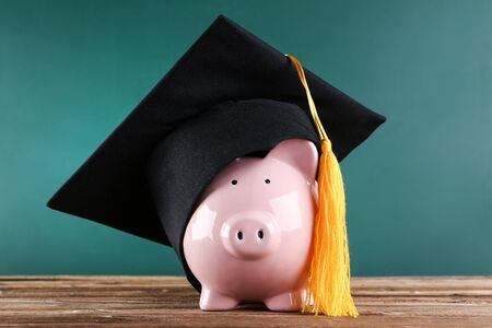 Piggybank with graduation cap on brown wooden table