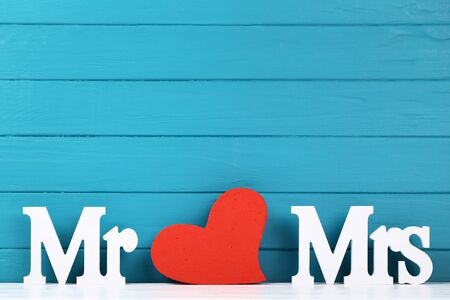 White letters Mr and Mrs with red heart on blue wooden background Stock fotó