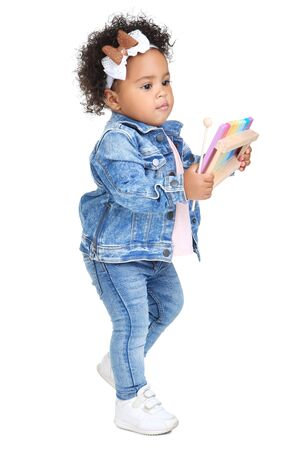 Beautiful baby girl with musical toy on white background Standard-Bild