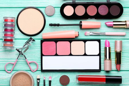 Different makeup cosmetics on mint wooden table
