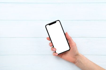 Smartphone in female hand on wooden background