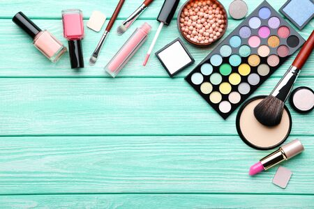 Different makeup cosmetics on mint wooden table Reklamní fotografie