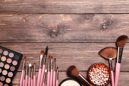 Makeup brushes with palette on brown wooden table