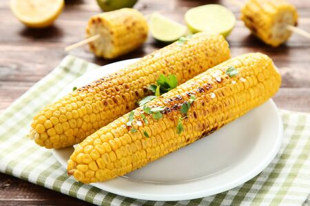 Grilled corn with green parsley leafs on brown wooden table