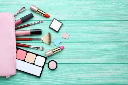 Make-up-Kosmetik auf mintfarbenem Holztisch