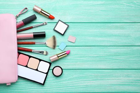 Makeup cosmetics on mint wooden table Stock Photo