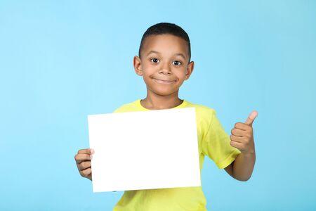 Cute american boy with blank board on blue background