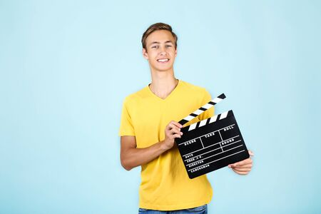 Young man with clapper board on blue background