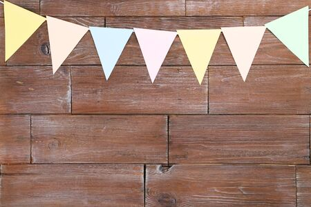 Colorful paper flags hanging on brown wooden background Stock Photo