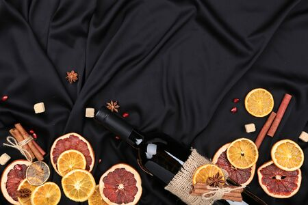 Dried citrus fruits with cinnamon, star anise and bottle of wine on black satin fabric background Stock fotó