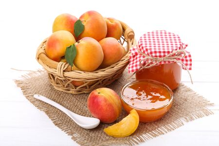 Jam in bowl and apricots on white wooden table