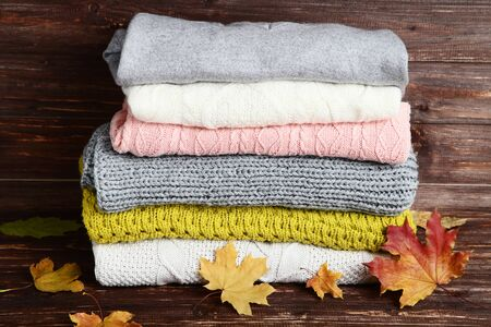 Stack of folded sweaters with maple leafs on wooden table Archivio Fotografico