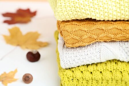 Stack of folded sweaters with autumn leafs and chestnut