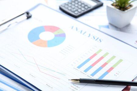 Gráfico financiero y tablas en el portapapeles con lápiz y calculadora Foto de archivo