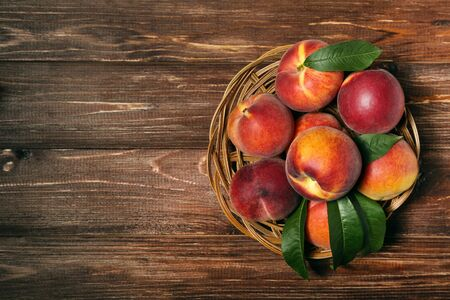 Fresh peaches with green leafs in basket on brown wooden table