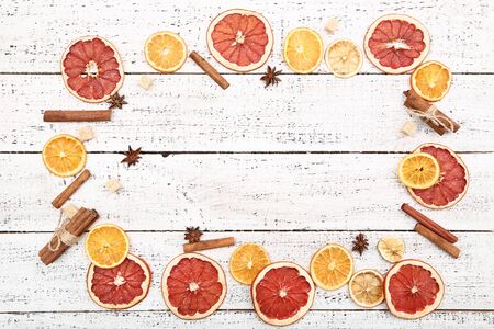 Dried citrus fruits with cinnamon, star anise and sugar cubes on white wooden table